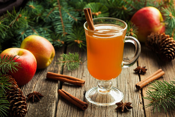 Fototapeta Hot apple cider traditional winter season drink with cinnamon and anise. Homemade healthy organic warm spice beverage. Christmas or thanksgiving holiday decoration on vintage wooden background