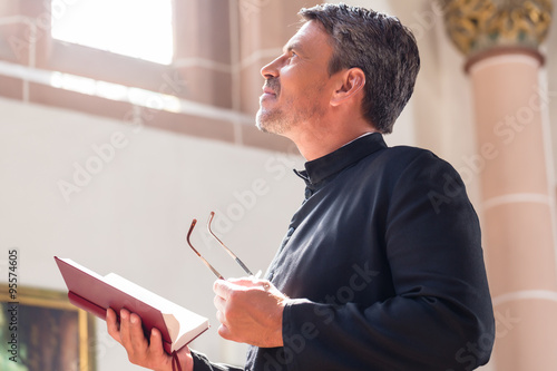 Fotografie, Obraz Catholic priest reading bible in church
