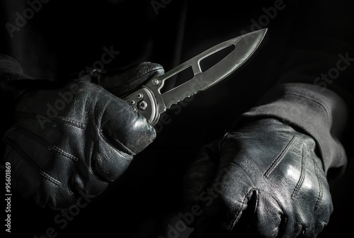 Photo  Assassin Holding Knife with Black Leather Gloves