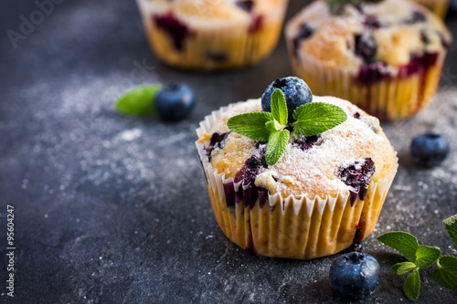 Photo  Blueberry muffins with powdered sugar and fresh berry