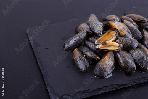 fresh seafood mussels on a black stone. top view, side view. space for inscriptions.Mytilus edulis