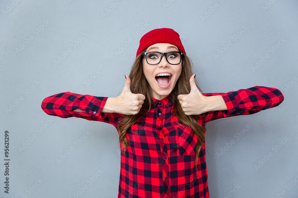 Fototapeta Cheerful hipster woman showing thumbs up