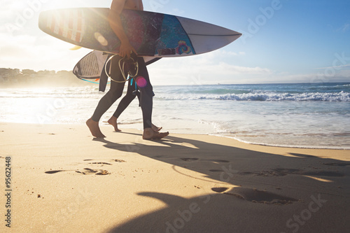 Australian surfers walking along Bondi Beach