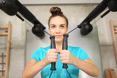 Fototapeta Rehabilitacja, trening z gumami. Kobieta trenuje w sali gimnastycznej obraz