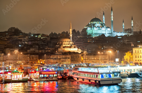 Poster Turquie Istanbul skyline from Galata bridge over Golden Horn by night, with Suleymaniye mosque and fish boat restaurants in Eminonu