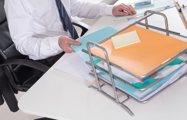 Businessman taking a record of his paper tray