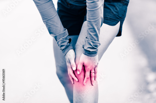 Fotografiet  Knee pain, woman holding sore and painful leg