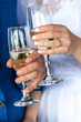 Man and woman drinking champagne. In the picture, close-up hands with glasses. They are celebrating their wedding anniversary.