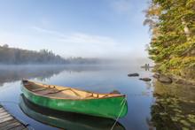 Green Canoe Tied To Dock