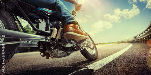 Photo  Biker riding motorcycle on an empty road at sunset