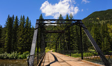 Black Steel Bridge Spans Gallatin River In Gallatin Valley.  Mountains Rise In Background.
