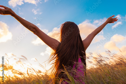 Fotografie, Obraz  Silhouette of woman with hands raised into sunset