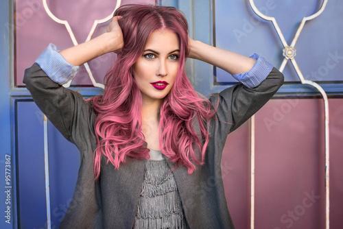 Naklejka premium Piękny modniś model z kędzierzawym różowym włosy pozuje przed kolorową ścianą
