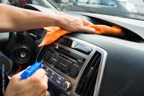Zdjęcie XXL Męski pracownik Czyści Samochodową deskę rozdzielczą