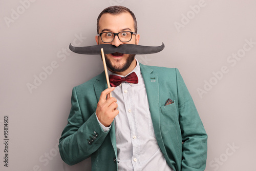 Photo  Excited man holding a fake mustache on his face