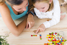 Young Mother And Daughter Playing With Sweets At Home.