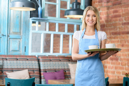 Pleasant waitress holding tray