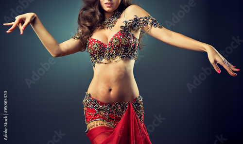 Fotobehang Dance School Graceful girl dancing belly dance . Belly dance in plastic movement of the dance. Red dress for belly dance with sequins and rhinestones and jewelry