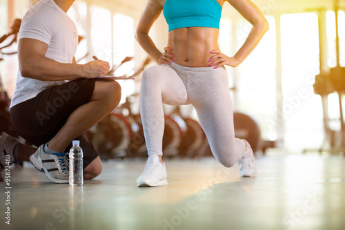 Fototapeta young sporty woman with trainer exercise