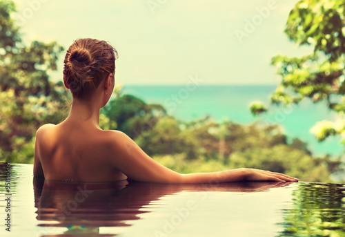 Foto op Aluminium Bali Beautiful girl rests in the swimming pool, sunbathing. Spa treatments.