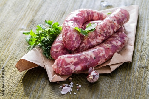 obraz dibond Raw sausages with herbs and spices