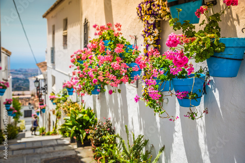 Picturesque street of Mijas with flower pots in facades. Andalus