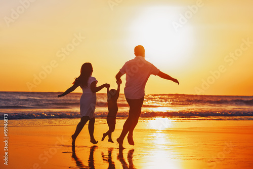 Fototapeta Happy family - father, mother, baby son hold hands and run with fun along edge of sunset sea on black sand beach. Active parents and people outdoor activity on tropical summer vacations with children. obraz na płótnie