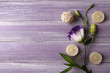 Spa composition of candles and flower on purple wooden background