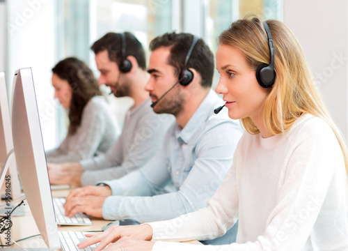 Foto  Young attractive woman working in a call center