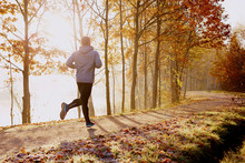 Man Running In Park At Autumn Morning