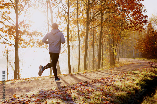 Leinwand Poster Man running in park at autumn morning