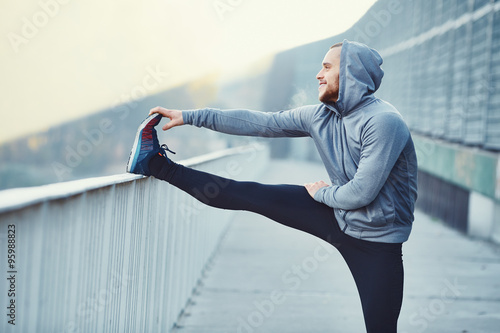 Photo Male runner doing stretching exercise