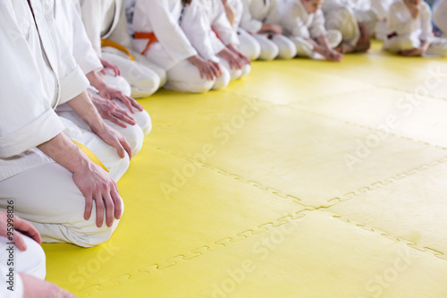 Poster de jardin Combat People in kimono sitting on tatami on martial arts seminar