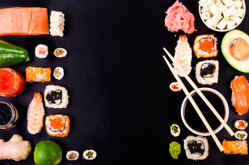 Fototapeta Sushi set, soy sauce, ginger, wasabi on black background. Free space for your text. Food frame