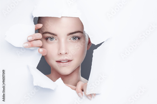 Fototapeta woman looking out from behind a hole in a paper sheet obraz
