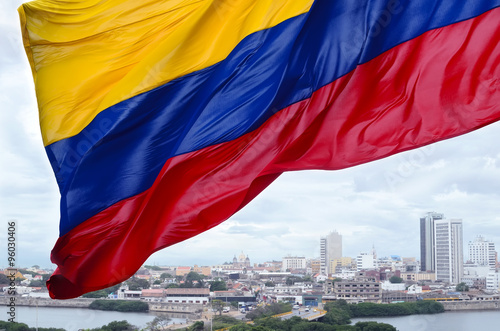 Fotografía  Colombian flag waving on the wind and modern Cartagena district
