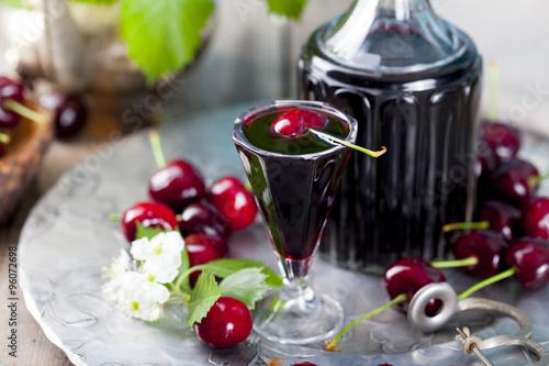 Fotografie, Obraz  Cherry homemade liquor in a vintage bottle with fresh cherries.