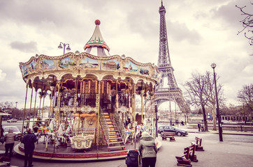 FototapetaParis, France - March 18, 2012: Children accompanied by their parents and grandparents play the carousel of the Eiffel Tower in Paris on a wet and cloudy day in March