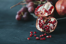 Fresh Red Pomegranate Fruit On Dark Blue Colored Table