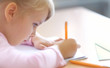 Cute five years old blonde girl sitting at classroom