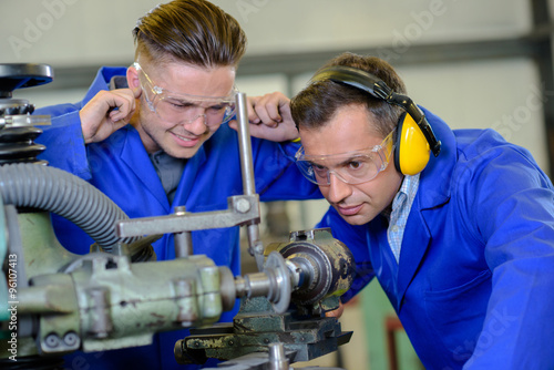 Photo Engineer using machine apprentice with fingers in ears