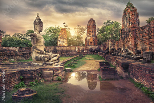 Fotografiet ancient Buddha statue and old Wat Mahathat pagoda in history temple of  Ayutthaya Historical Park,world heritage sites of unesco