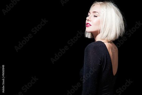 Fotografia, Obraz  Blonde in a black dress with an open back on a black background