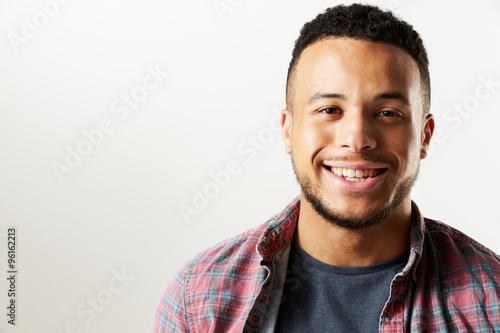 Studio Portrait Of Smiling Man Against White Background