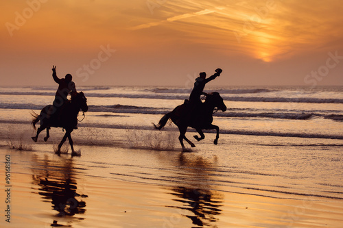 Fotografía  Silhouette of a horse and rider galloping on beach at sunset.