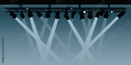A background silhouette illustration of a spotlight rig shining beams down into the darkness.