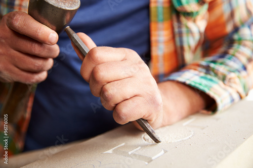 Valokuva  Close Up Of Stone Mason At Work On Carving In Studio