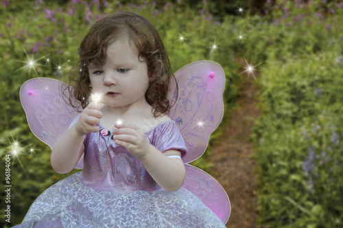 Fotografie, Tablou  Girl gazing at a glowing fairy in her hand/Girl gazing at a glowing fairy in her hand, dressed in a fairy princess dress