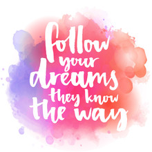 Follow Your Dreams, They Know The Way. Inspirational Quote About Life And Love.  Modern Calligraphy Text, Handwritten With Brush On Pink And Orange Watercolor Splash Background With Bokehs