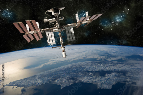 Obraz A depiction of the space shuttle docked at the international space station orbiting Earth. -  Elements of this image furnished by NASA - fototapety do salonu